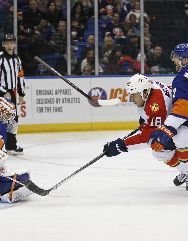 New York Islanders defenseman Andrew MacDonald, right, loses his stick while defending against Florida Panthers center Shawn Matthias (18) who eases the puck past Islanders goalie Anders Nilsson (45), of Sweden, for the go-ahead goal in the third period of an NHL hockey game in Uniondale, N.Y., Sunday, March 2, 2014. The Panthers defeated the Islanders 5-3