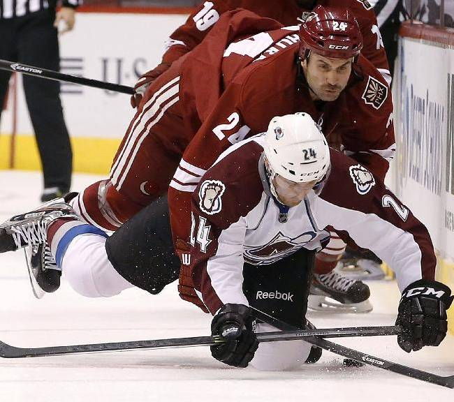 Colorado Avalanche's Marc-Andre Cliche, bottom, gets taken down by Phoenix Coyotes' Kyle Chipchura during the second period of an NHL hockey game Thursday, Nov. 21, 2013, in Glendale, Ariz