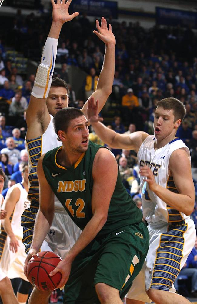 North Dakota State forward Marshall Bjorklund looks to pass the ball as South Dakota State forward Cody Larson, left, and guard Jake Bittle defend during the first half of an NCAA college basketball game at Frost Arena in Brookings, S.D., Saturday, Jan. 25, 2014. North Dakota State went on to beat South Dakota State 85-77