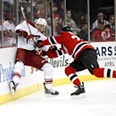 Phoenix Coyotes right wing David Moss, left, hits the board while competing for the puck with New Jersey Devils' Eric Gelinas during the first period of an NHL hockey game, Thursday, March 27, 2014, in Newark, N.J The Associated Press