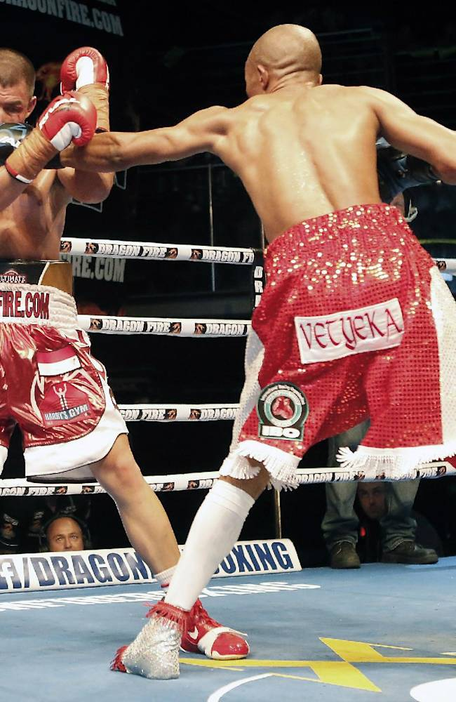 Indonesia's WBO Super featherweight champion Chris Johns, left, in action with IBO champion South African's Simpiwe Vetyeka,  during their Super Featherweight title fight in Perth, Australia, Friday, Dec. 6, 2013. Johns lost the bout after his trainer through in the towel after the sixth round