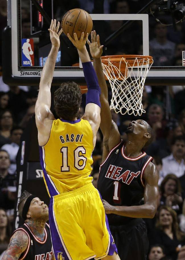 Los Angeles Lakers center Pau Gasol (16) shoots against Miami Heat center Chris Bosh (1) during the second quarter of an NBA basketball game in Miami, Thursday, Jan. 23, 2014