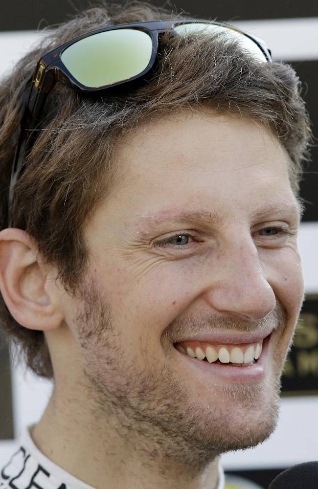Lotus driver Romain Grosjean of France smiles as he is interviewed by a journalist  following the second practice session at the Korean Formula One Grand Prix at the Korean International Circuit in Yeongam, South Korea, Friday, Oct. 4, 2013