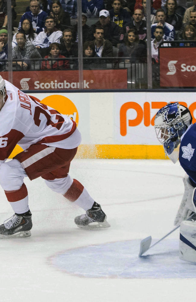 Detroit Red Wings' Tomas Jurco, left, scores against Toronto Maple Leafs goaltender James Reimer during first period NHL hockey action in Toronto on Saturday, Dec 21, 2013