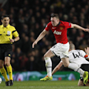 Manchester United's Phil Jones, centre takes the ballast a falling Donetsk's Yaroslav Rakitskiy during their Champions League group A soccer match between Manchester United and Shakhtar Donetsk at Old Trafford Stadium, Manchester, England, Tuesday, Dec. 1