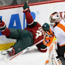Minnesota Wild's Charlie Coyle, left, trips over the stick of Philadelphia Flyers goalie Ray Emery in the first period of an NHL hockey game, Tuesday, Dec. 23, 2014, in St. Paul, Minn. (AP Photo/Jim Mone)