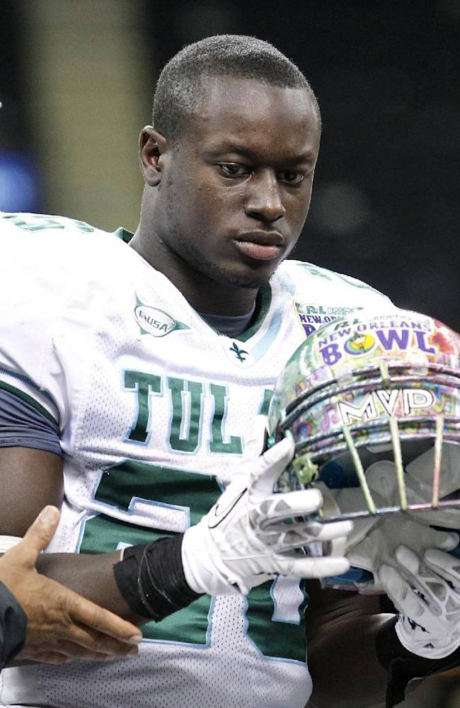 Tulane running back Orleans Darkwa (26) is presented the MVP trophy after the New Orleans Bowl NCAA college football game, in New Orleans, Saturday, Dec. 21, 2013. Louisiana-Lafayette defeated Tulane 24-21