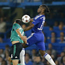 Schalke's Kaan Ayhan, left, and Chelsea's Didier Drogba jump for the ball during the Champions League Group G soccer match between Chelsea and Schalke 04 at Stamford Bridge stadium in London Wednesday, Sept. 17, 2014