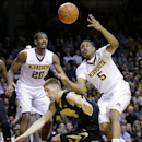 Minnesota guard Daquein McNeil (5) loses control of the ball as he collides with Iowa forward Jarrod Uthoff, center, in front of Minnesota guard Austin Hollins (20) during the first half of an NCAA college basketball game in Minneapolis, Tuesday, Feb. 25, 2014. (AP Photo/Ann Heisenfelt)