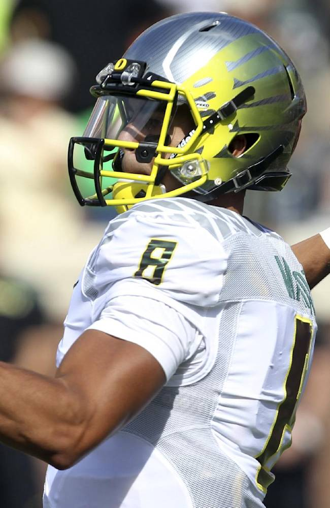 In this Sept. 7, 2013, file photo, Oregon quarterback Marcus Mariota (8) throws the ball during the first half against Virginia in an NCAA college football game at Scott Stadium in Charlottesville, Va. Mariota is ranked fifth nationally with an average of 383.7 total offensive yards per game, guiding an offense averaging 61.3 points per game