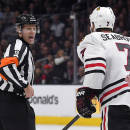 Official Gord Dwyer, left, and Chicago Blackhawks defenseman Brent Seabrook yell at each other after Seabrook was called for closing his hand around the puck during the second period of an NHL hockey game against the Los Angeles Kings, Wednesday, Jan. 28, 2015, in Los Angeles. (AP Photo/Mark J. Terrill)
