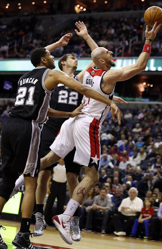 Washington Wizards center Marcin Gortat, right, from Poland, drives to the basket between San Antonio Spurs forward Tim Duncan (21) and center Tiago Splitter (22), from Brazil, in the first half of an NBA basketball game on Wednesday, Feb. 5, 2014, in Washington