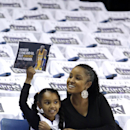 Los Angeles Lakers fan Malisiyana Edwards, 7, joined by her mother Alisia, holds up an image of her favorite player, Lakers guard Kobe Bryant, while seated among Sacramento Kings give away t-shirts before an NBA basketball game in Sacramento, Calif., Frid