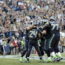Fans cheer as Seattle Seahawks running back Marshawn Lynch (24) celebrates with teammates after Lynch scored the game-winning touchdown in overtime of an NFL football game against the Denver Broncos, Sunday, Sept. 21, 2014, in Seattle. The Seahawks won 26