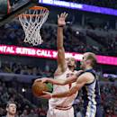 Chicago Bulls center Joakim Noah (13) forces Memphis Grizzlies shooting guard Nick Calathes, right, to pass the ball to teammate Jon Leuer (30) during the first half of an NBA basketball game on Friday, March 7, 2014, in Chicago. (AP Photo/Charles Rex Arbogast)