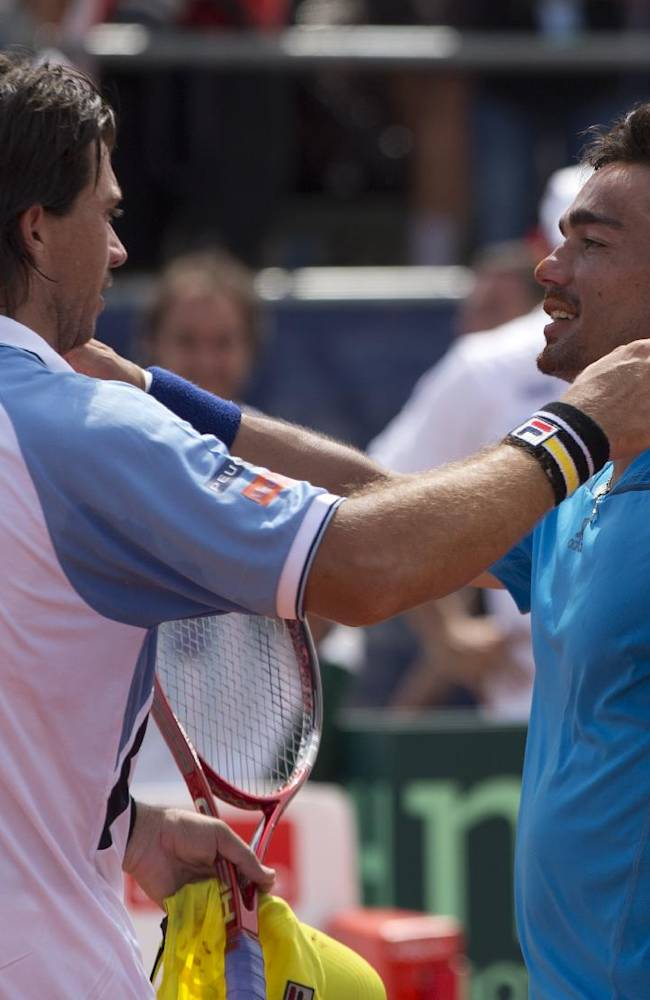 Argentina's Carlos Berlocq, left, and  Italy's Fabio Fognini embrace at the end of their Davis Cup singles match, in Mar del Plata, Argentina, Sunday, Feb. 2, 2014. Fognini defeated Berlocq 7-6, 4-6, 6-1, 6-4 to give Italy a 3-1 victory