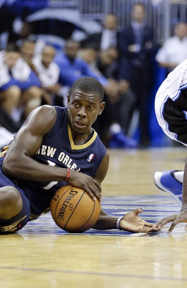 New Orleans Pelicans' Jrue Holiday, left, grabs a loose ball in front of Orlando Magic's Victor Oladipo, right, during the second half of an NBA basketball game in Orlando, Fla., Friday, Nov. 1, 2013. Orlando Magic won the game 110-90