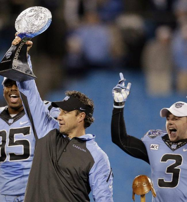 North Carolina head coach Larry Fedora, center, raises the trophy as he celebrates with Kareem Martin, left, and Ryan Switzer, right, after defeating Cincinnati in the Belk Bowl NCAA college football game in Charlotte, N.C., Saturday, Dec. 28, 2013. North Carolina won 39-17