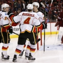 Calgary Flames' Mikael Backlund, right front, of Sweden, celebrates his goal against Arizona Coyotes' Mike Smith, right, with teammates Kris Russell (4); Jiri Hudler (24), of the Czech Republic; and Johnny Gaudreau, left, during the second period of an NH