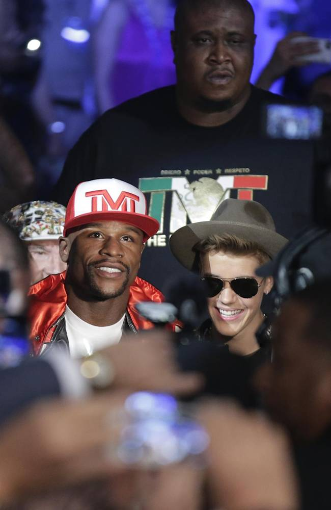 Floyd Mayweather Jr., center left, is joined by Justin Bieber as he enters the arena for his WBC-WBA welterweight title boxing fight against Marcos Maidana Saturday, May 3, 2014, in Las Vegas