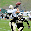 New Orleans Saints tight end Jimmy Graham (80) receives a pass over strong safety Kenny Vaccaro (32) during NFL football training camp in White Sulphur Springs, W.Va., Sunday, July 27, 2014 The Associated Press