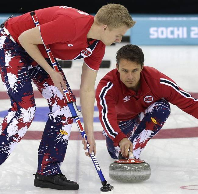 Norway's skip Thomas Ulsrud, right, delivers the rock while Haavard Vad Petersson, left, prepares to sweep the ice during the men's tiebreaker curling match against Britain at the 2014 Winter Olympics, Tuesday, Feb. 18, 2014, in Sochi, Russia