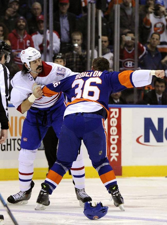 New York Islanders left wing Eric Boulton (36) and Montreal Canadiens right wing George Parros (15) fight in the first period of an NHL hockey game at Nassau Coliseum in Uniondale, N.Y., Saturday, Dec. 14, 2013