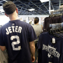 A New York Yankees fan wearing a Derek Jeter shirt walks past Jeter T-shirts for sale in the Yankees gift shop during a spring training baseball exhibition game between Yankees and Philadelphia Phillies, Wednesday, March 4, 2015, in Tampa, Fla. (AP Photo/Lynne Sladky)