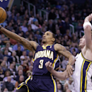 Indiana Pacers' George Hill (3) lays the ball up as Utah Jazz's Gordon Hayward (20) looks on in the second quarter during an NBA basketball game Wednesday, Dec. 4, 2013, in Salt Lake City The Associated Press