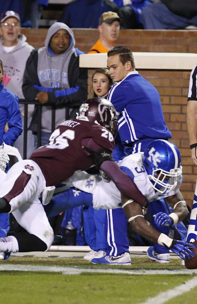 Kentucky running back Jojo Kemp (3) leaps past Mississippi State defensive back Kendrick Market (26) for a 14-yard touchdown run in the second half of their NCAA college football game at Davis Wade Stadium in Starkville, Miss., Thursday, Oct. 24, 2013. Mississippi State won 28-22