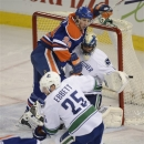 Edmonton Oilers' Ryan Smyth, 94, falls into the Vancouver Canucks goalie Roberto Luongo during second period NHL hockey actio