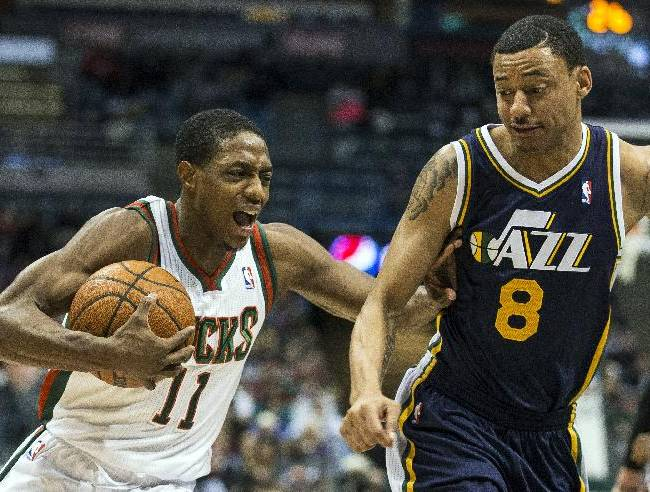 Milwaukee Bucks' Brandon Knight, left, is fouled by Utah Jazz Diante Garrett during the first half of an NBA basketball game Monday, March 3, 2014, in Milwaukee
