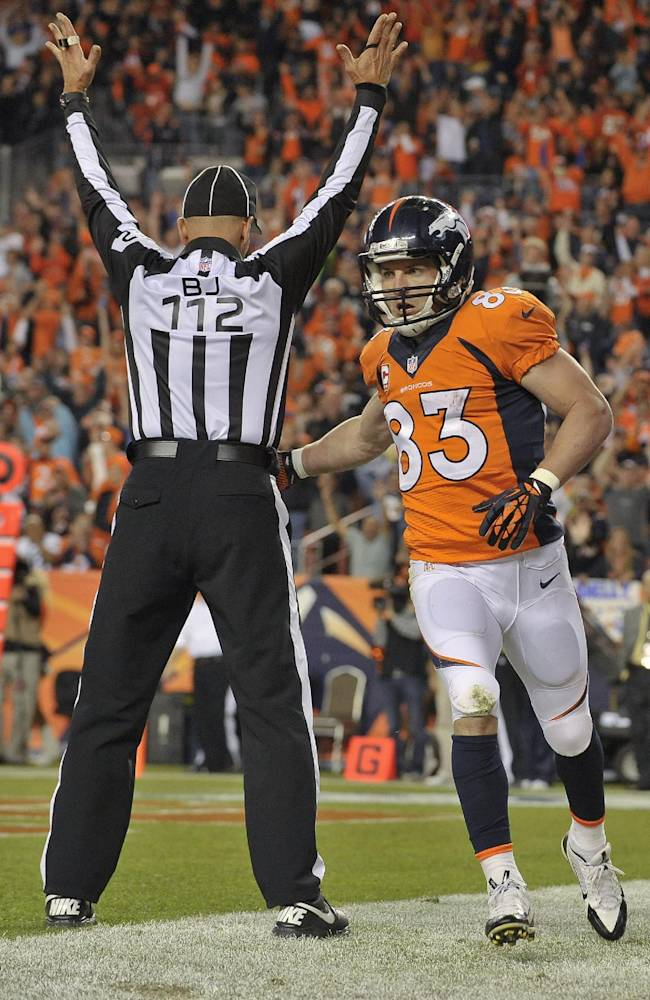 Denver Broncos wide receiver Wes Welker (83) hands the ball to back judge Tony Steratore (112) after catching a touchdown pass against the Oakland Raiders in the second quarter of an NFL football game, Monday, Sept. 23, 2013, in Denver