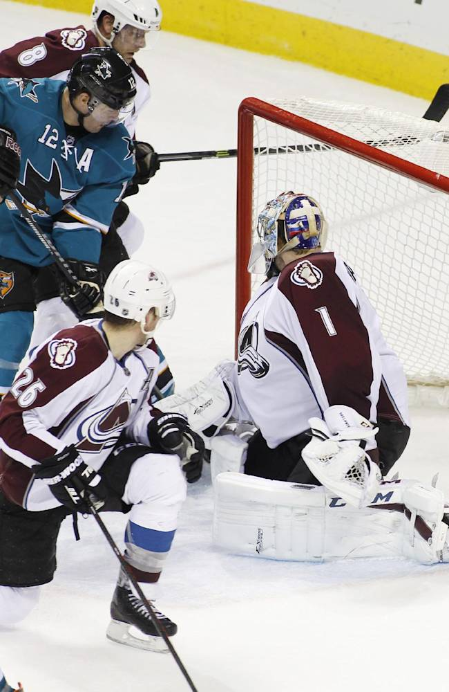 San Jose Sharks' Joe Pavelski, far left, scores a goal past Colorado Avalanche goalie Semyon Varlamov, to tie the game late in the third period of an NHL hockey game, Monday, Dec. 23, 2013, in San Jose, Calif