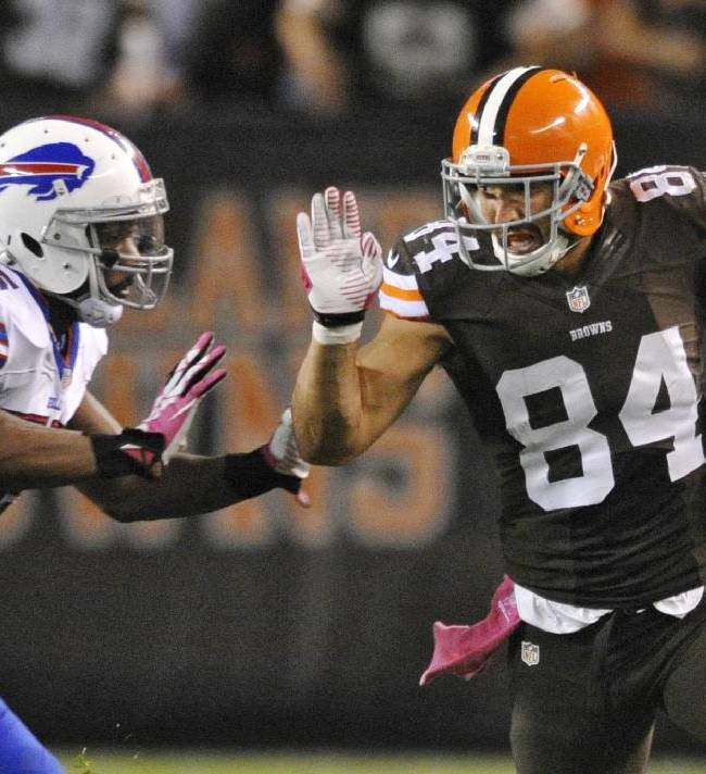 Cleveland Browns tight end Jordan Cameron (84) looks to fend off Buffalo Bills outside linebacker Jerry Hughes on a reception good for a first down in the second quarter of an NFL football game Thursday, Oct. 3, 2013, in Cleveland