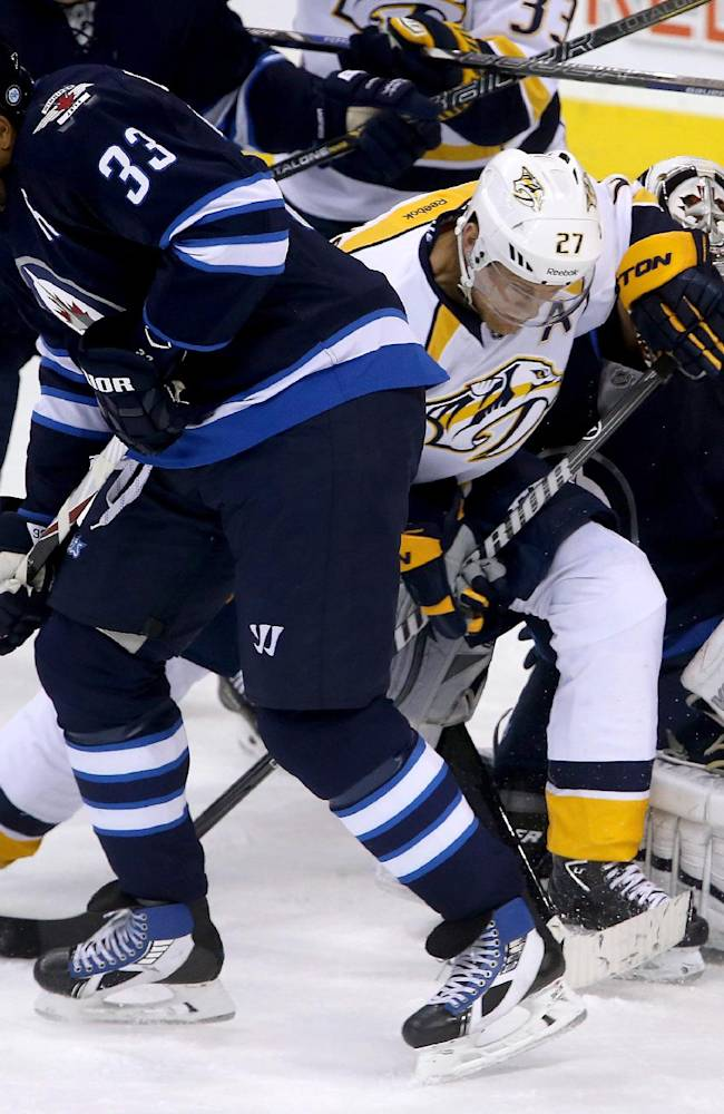 Winnipeg Jets' Dustin Byfuglien (33) blocks a shot as Nashville Predators' Patric Hornqvist (27) screens goaltender Ondrej Pavelec (31) during first period NHL hockey game in Winnipeg, Manitoba, Sunday, Oct. 20, 2013
