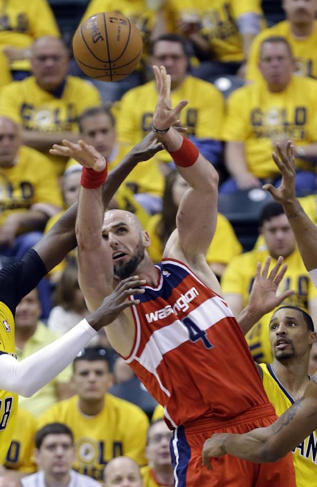 Washington Wizards center Marcin Gortat, center, makes a pass over Indiana Pacers center Ian Mahinmi, left, and Indiana Pacers forward David West, right, during the second half of game 1 of the Eastern Conference semifinal NBA basketball playoff series in Indianapolis, Monday, May 5, 2014. The Wizards defeated the Pacers 102-96