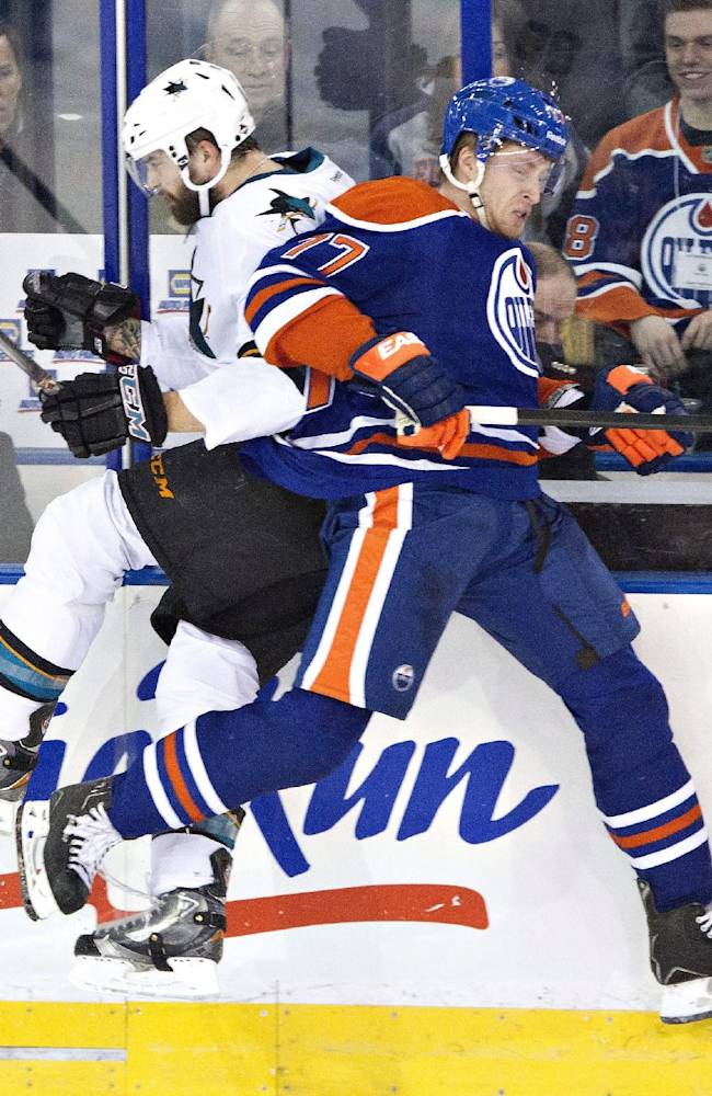 San Jose Sharks' Brent Burns (88) is checked by Edmonton Oilers' Anton Belov (77) during the second period of an NHL hockey game Wednesday, Jan. 29, 2014, in Edmonton, Alberta