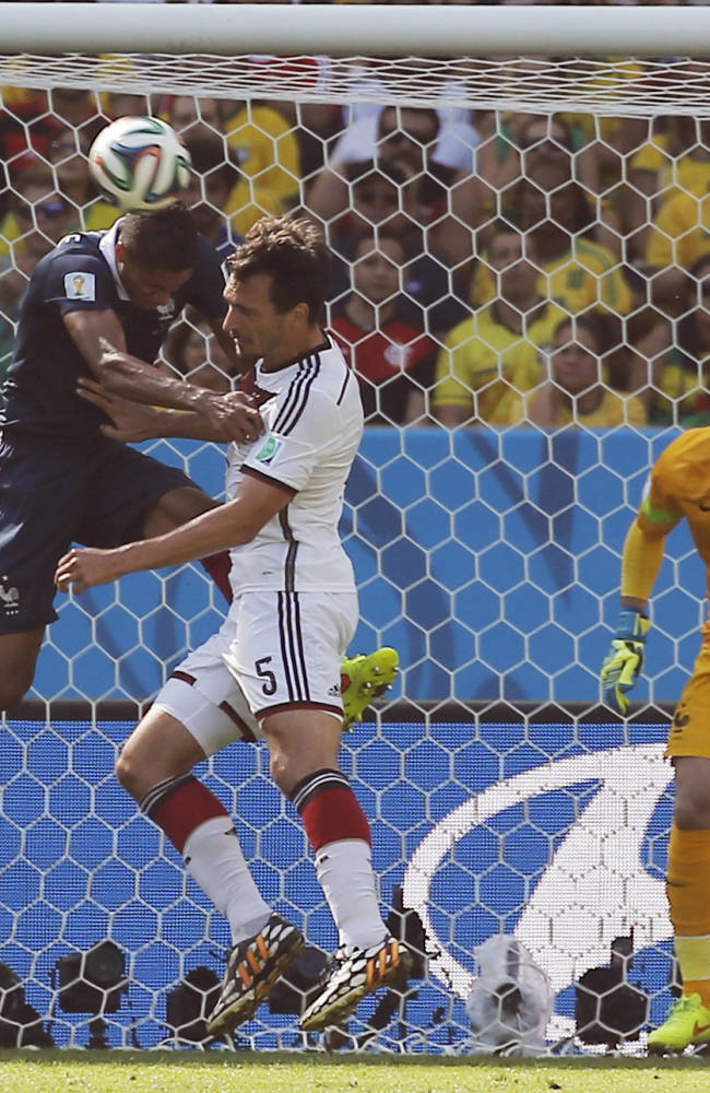 Germany's Mats Hummels, center, scores the opening goal during the World Cup quarterfinal soccer match between Germany and France at the Maracana Stadium in Rio de Janeiro, Brazil, Friday, July 4, 2014