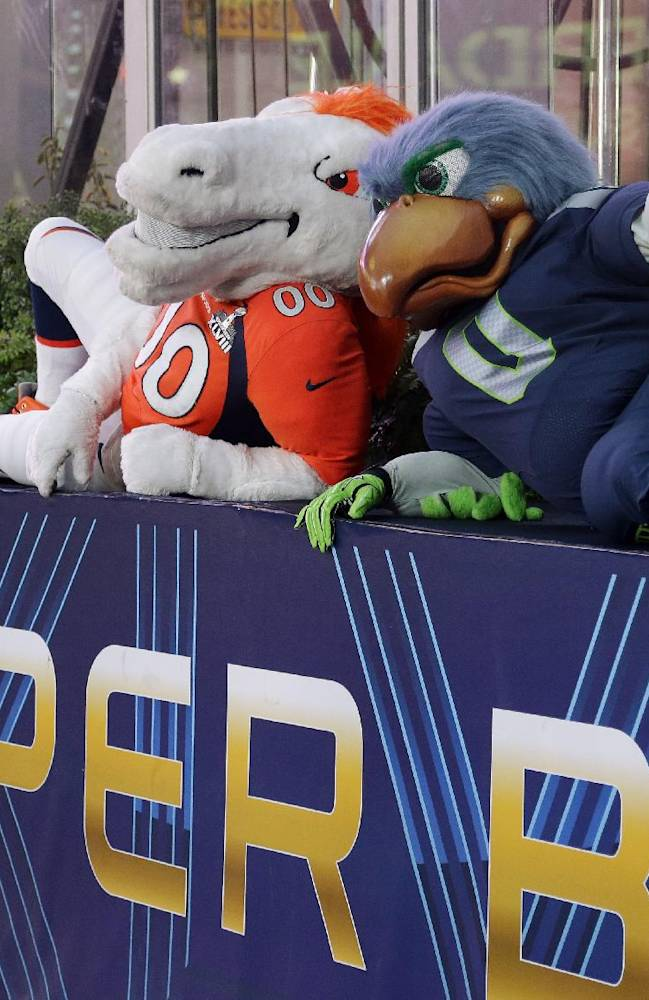 Blitz, right, the Seattle Seahawks mascot, is sits with Miles, left, the Denver Broncos mascot, Friday, Jan. 31, 2014 on top of a Super Bowl sign during a live broadcast of Good Morning America at Times Square in New York. The Seattle Seahawks will play the Broncos Sunday in the NFL Super Bowl XLVIII football game in East Rutherford, N.J