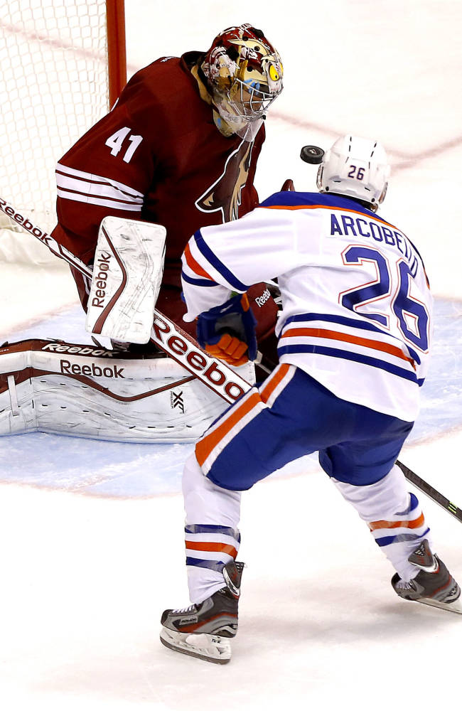 Edmonton Oilers' Mark Arcobello (26) shoots on goal as Phoenix Coyotes goalie Mike Smith defends during the third period of an NHL hockey game Saturday, Oct. 26, 2013, in Glendale, Ariz. The Coyotes won 5-4