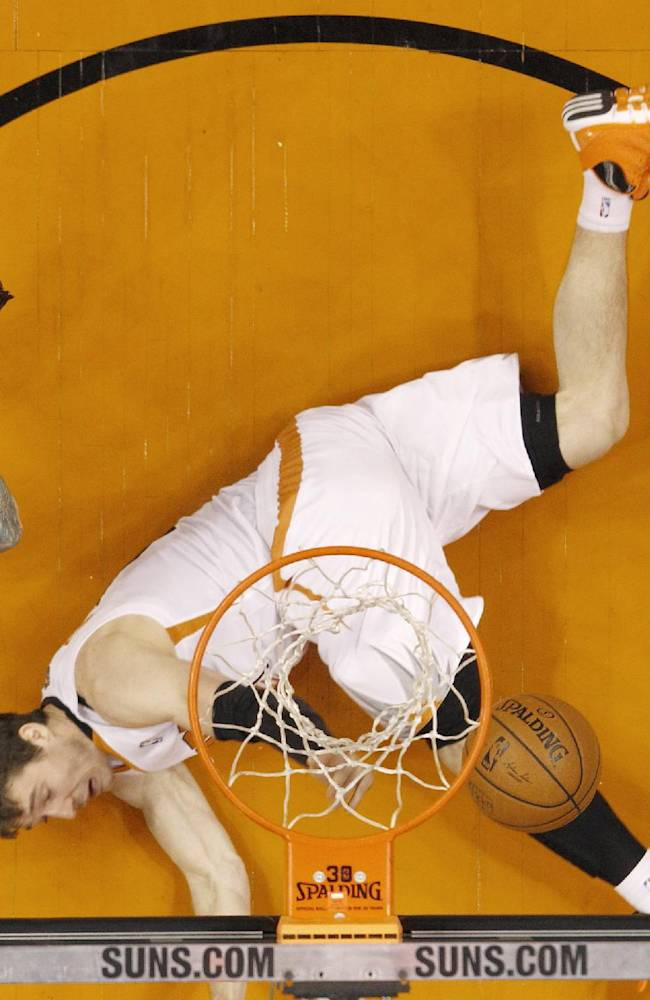 Phoenix Suns' Goran Dragic, right, of Slovenia, falls to the floor after being fouled by Miami Heat's Chris Andersen, left, during the first half of an NBA basketball game Tuesday, Feb. 11, 2014, in Phoenix.  The Heat defeated the Suns 103-97