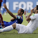 In this June 24, 2014 file photo, Uruguay's Luis Suarez holds his teeth after biting Italy's Giorgio Chiellini's shoulder during the group D World Cup soccer match between Italy and Uruguay in Natal, Brazil. Just days after his two goals helped Uruguay de