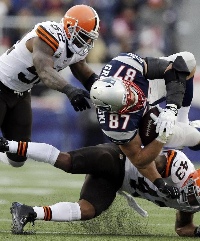 In this Sunday. Dec. 8, 2013, file photo, Cleveland Browns safety T.J. Ward (43) goes low as he hits New England Patriots tight end Rob Gronkowski (87) after a catch in the third quarter of an NFL football game in Foxborough, Mass. Joining in on the play is Browns linebacker D'Qwell Jackson (52). Gronkowski's season ended abruptly Sunday with a knee injury when he took a low hit from Ward. No penalty was called