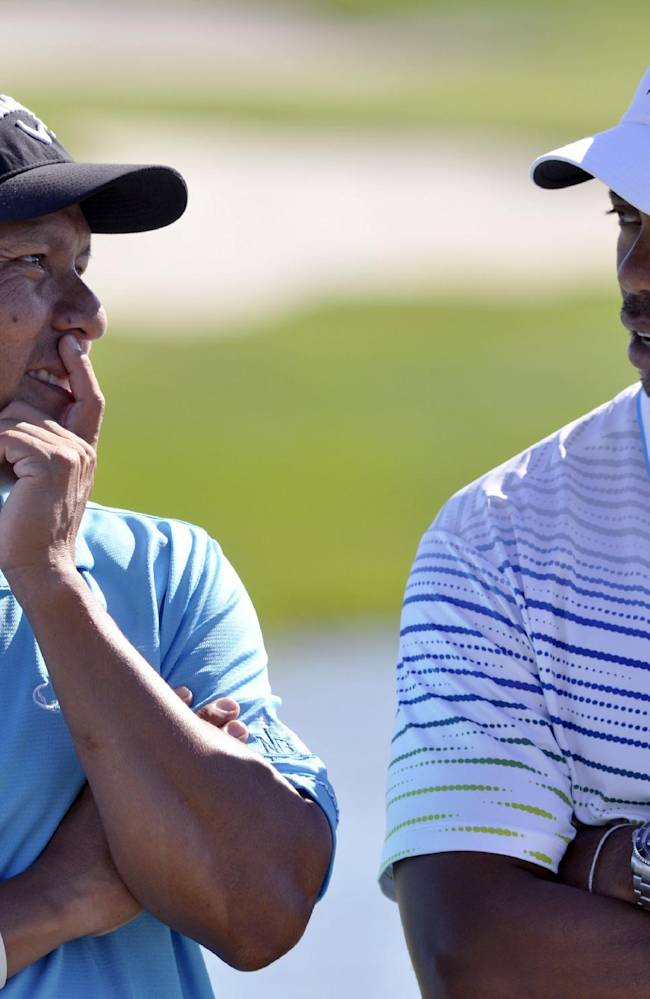 Notah Begay III, left, and Tiger Woods talk after wining the fifth annual Notah Begay III Foundation Challenge at Atunyote Golf Club at Turning Stone Resort and Casino in Verona, N.Y., Wednesday, Aug. 29, 2012