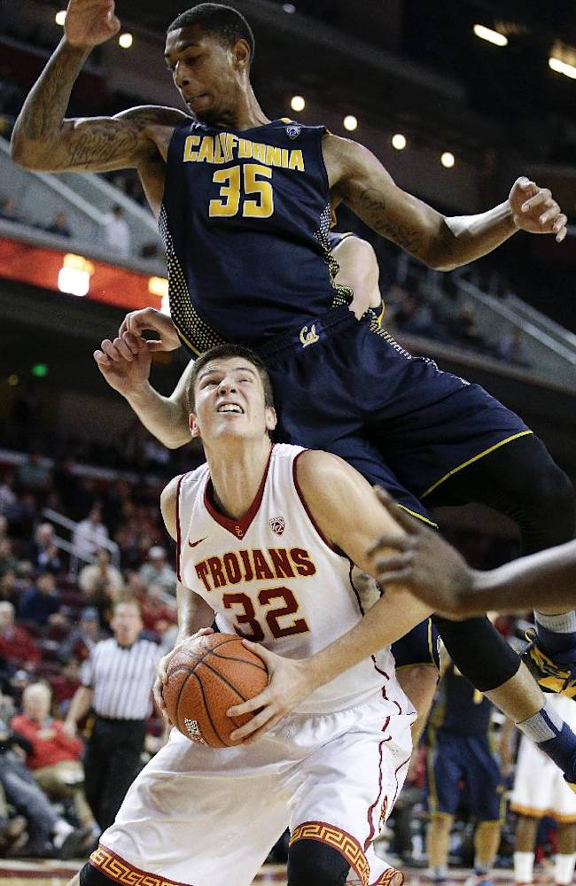 Southern California's Nikola Jovanovic, bottom, of Serbia, is fouled by California's Richard Solomon during the second half of an NCAA college basketball game on Wednesday, Jan. 22, 2014, in Los Angeles. USC won 77-69