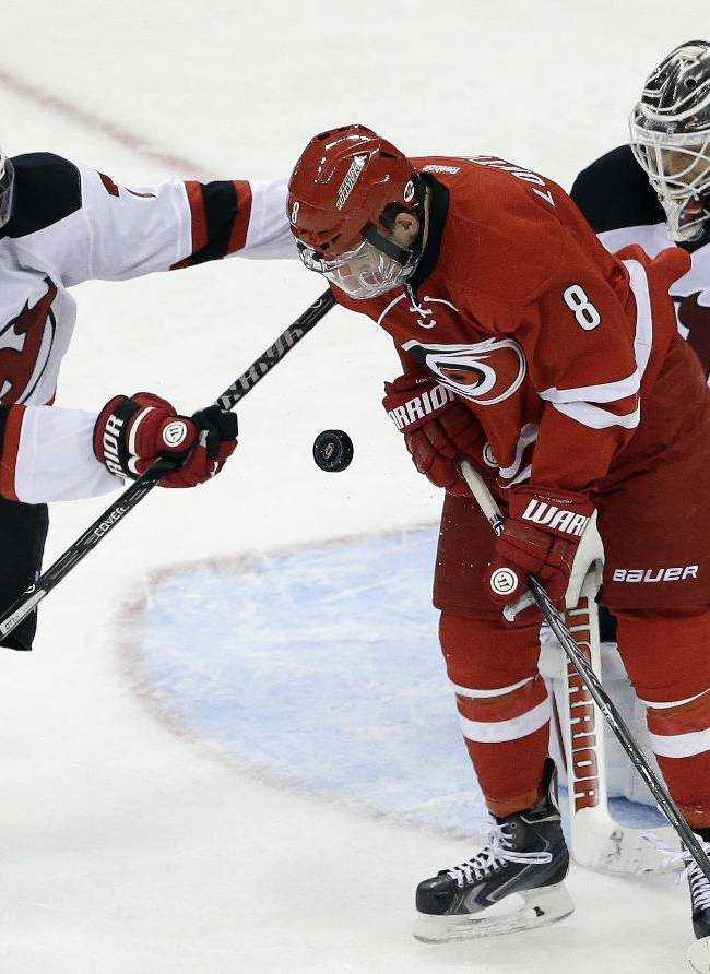 Carolina Hurricanes' Andrei Loktionov (8), of Russia, tries to score as New Jersey Devils' Mark Fayne (7) and goalie Cory Schneider (35) defend during the third period of an NHL hockey game in Raleigh, N.C., Saturday, April 5, 2014. New Jersey won 3-1