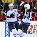 Winnipeg Jets' Blake Wheeler, left, celebrates with Toby Enstrom after Wheeler scored a goal during the first period of an NHL hockey game against the New Jersey Devils Thursday, Oct. 30, 2014, in Newark, N.J The Associated Press