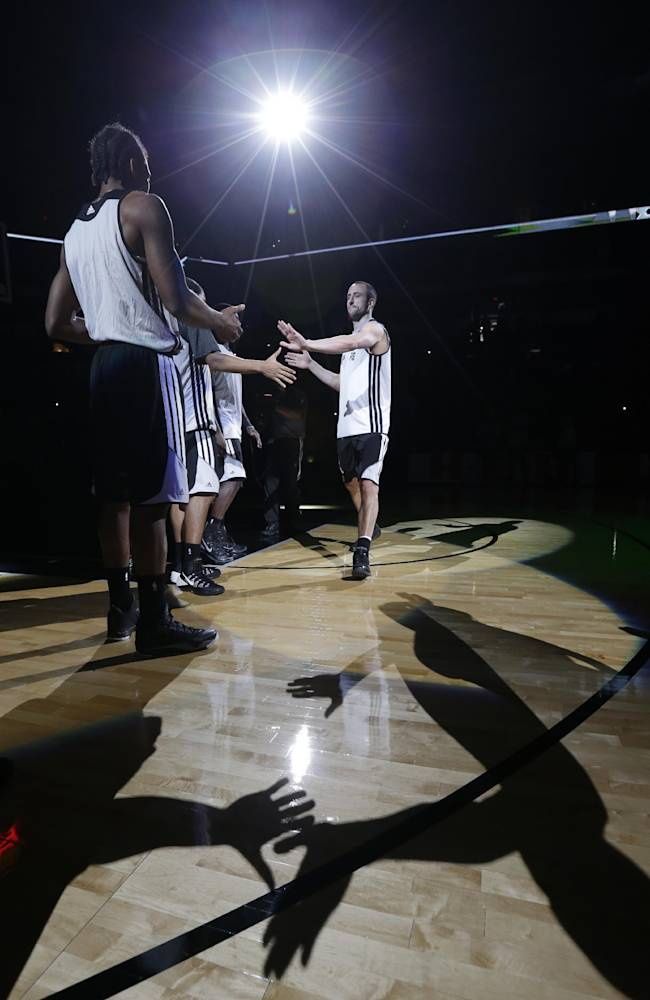 San Antonio Spurs' Manu Ginobili, right, of Argentina, shakes hands with teammates as he in introduced during an open NBA basketball practice, Sunday, Oct. 6, 2013, in San Antonio