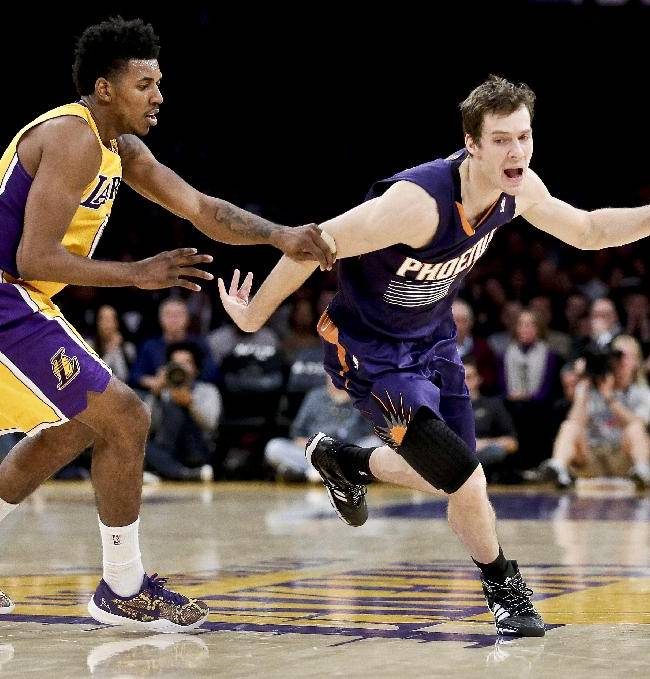 Los Angeles Lakers forward Nick Young, left, fouls Phoenix Suns guard Goran Dragic during the second half of an NBA basketball game in Los Angeles, Tuesday, Dec. 10, 2013